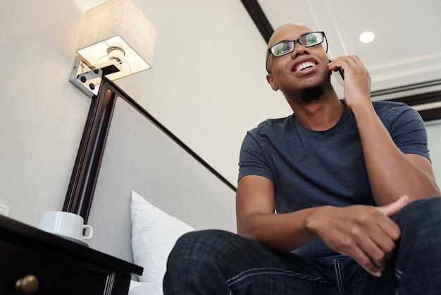 Vrolijke jonge man in glazen zittend op de rand van het bed en praten over phoe met collega of vriend, weergave van onderen