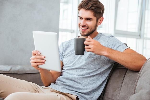 Vrolijke jonge man in grijs t-shirt zittend op de bank thuis. communicatie via tablet en lachend tijdens het drinken van een kopje koffie.