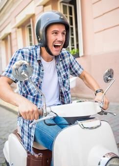 Vrolijke jonge man in helm rijdt op scooter in de stad.