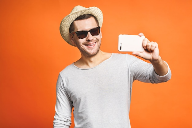 Vrolijke jonge man in hoed en zonnebril selfie met smartphone geïsoleerd op oranje achtergrond