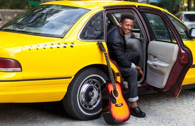 Vrolijke jonge man in interieur salon van auto met geopende deur van gele auto, op zoek naar een kant, in de buurt van gitaar.