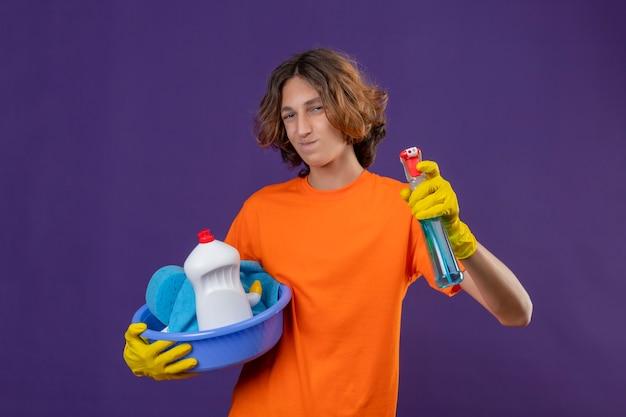 Vrolijke jonge man in oranje t-shirt die rubberen handschoenen draagt ?? die bekken met het schoonmaken van gereedschappen houdt en het schoonmaken van spray positief en gelukkig over paarse ruimte