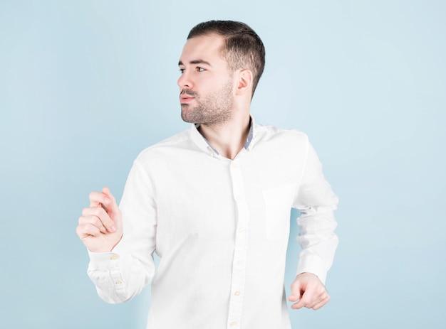 Vrolijke jonge man in shirt poseren op blauwe muur
