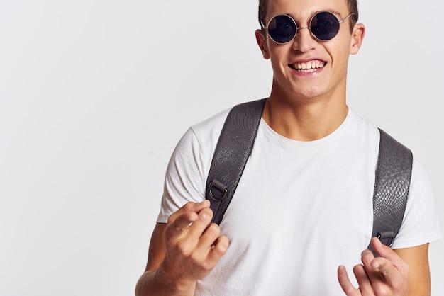 Vrolijke jonge man in zonnebril rugzak lifestyle mode kleding.