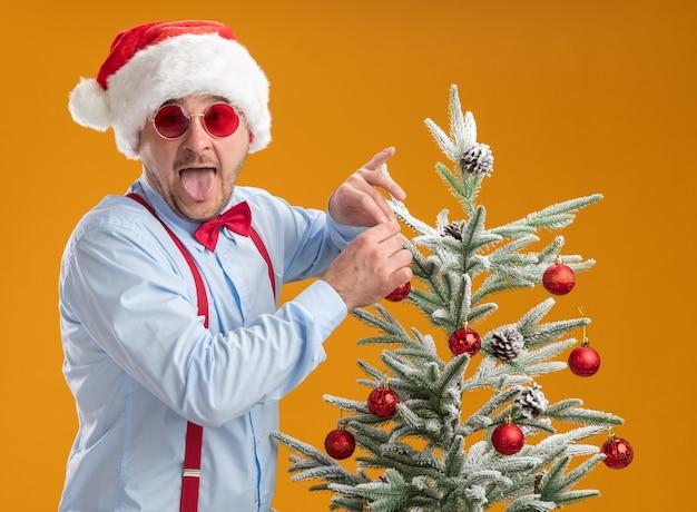Vrolijke jonge man met bretels strikje in kerstmuts en rode bril permanent in de buurt van kerstboom opknoping speelgoed op boom blij en verrast tong uitsteekt over oranje achtergrond