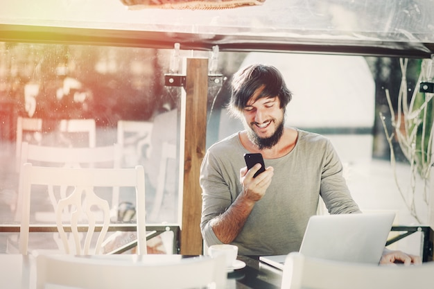Vrolijke jonge man met de smartphone glimlachend in zonlicht