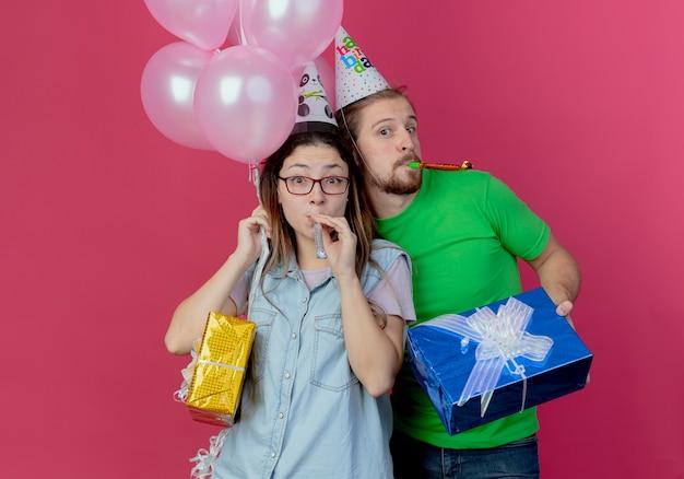 Vrolijke jonge man met feestmuts houdt geschenkdoos vast en blaast fluitje staande achter verrast jong meisje met helium ballonnen en geschenkdoos geïsoleerd op roze muur