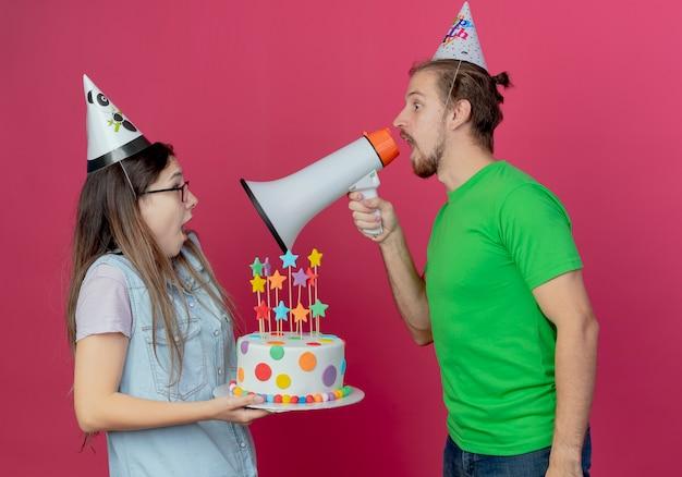 Vrolijke jonge man met feestmuts houdt vast en roept in luide spreker kijkend naar verrast jong meisje met feestmuts en met verjaardagstaart geïsoleerd op roze muur