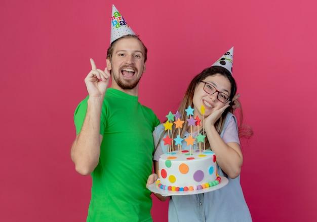 Vrolijke jonge man met feestmuts wijst naar boven en staat met blij jong meisje met feestmuts die verjaardagstaart houdt die op roze muur wordt geïsoleerd