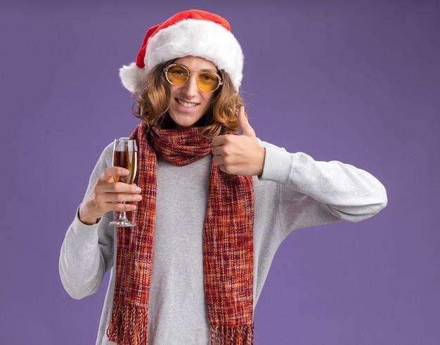 Vrolijke, jonge man, met, kerstmuts, en, gele bril, met, warme sjaal om zijn, nek, vasthouden, glas champagne, kijken naar, camera, het glimlachen, weergeven, beduimelt omhoog, staand, op, paarse achtergrond