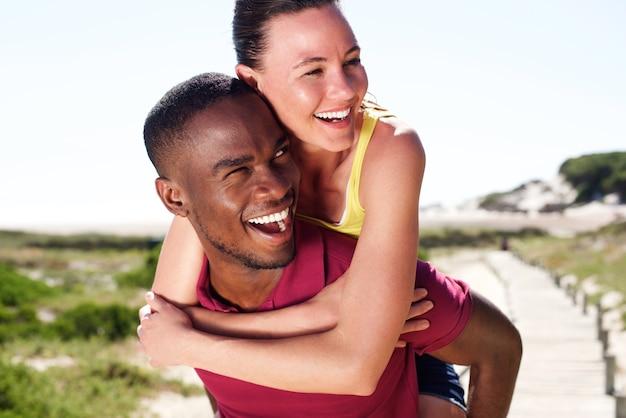 Vrolijke jonge man met mooie vriendin op zijn rug