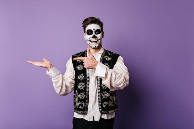 Vrolijke jonge man met oprechte glimlach wijst vinger naar zijn hand. binnenmomentopname van kerel met halloween-make-up met ruimte voor tekst op geïsoleerde muur.