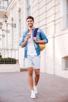 Vrolijke jonge man met rugzak wandelen en koffie drinken in de stad