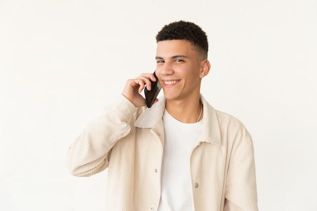 Vrolijke jonge man praten door smartphone