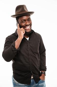 Vrolijke jonge man praten via de telefoon.