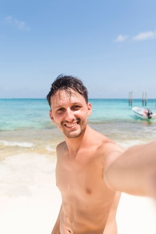 Vrolijke jonge man selfie te nemen op het strand