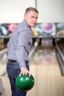 Vrolijke jonge man spelen bowlen.