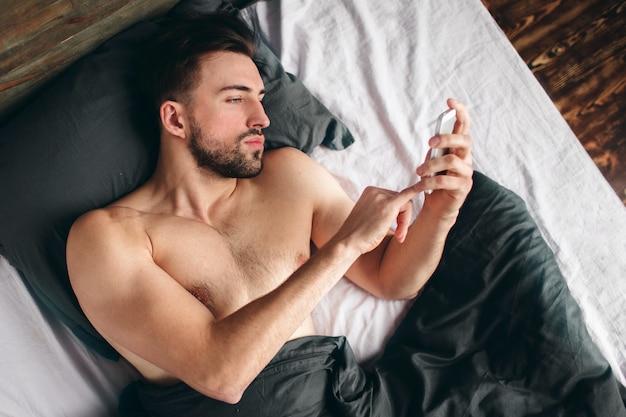 Vrolijke jonge man spreken door mobiel in slaapkamer. de knappe sportieve jonge kerel in ondergoed ligt op bed