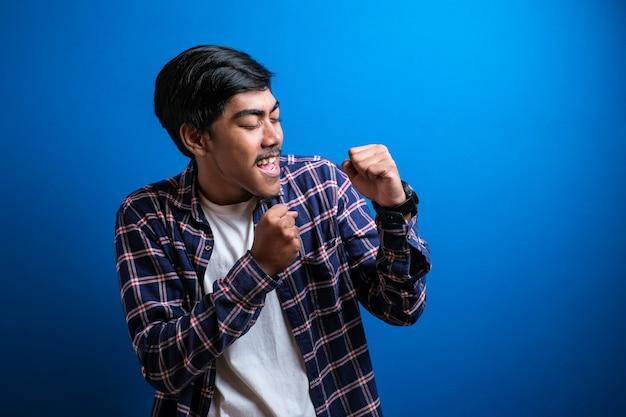 Vrolijke jonge man student in casual kleding geïsoleerd op blauwe achtergrond studio hief zijn arm op om zijn overwinning te vieren. de man danst vrolijk over het goede nieuws dat hij heeft ontvangen.