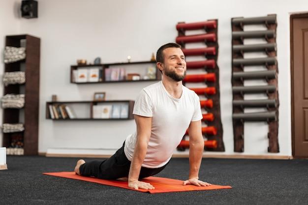 Vrolijke jonge man trainer doet yoga oefening in de fitness-studio.