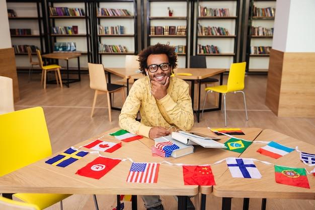 Vrolijke jonge man zit aan de tafel met boeken en vlaggen van landen in de bibliotheek