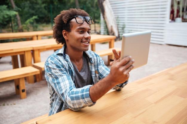 Vrolijke jonge man zit en met behulp van tablet buitenshuis