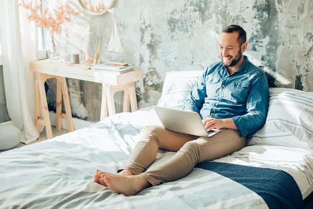 Vrolijke jonge man zit met een laptop op het bed en glimlacht terwijl hij naar het scherm kijkt