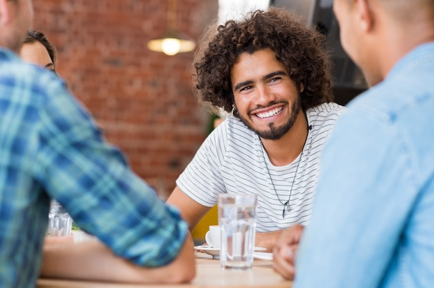 Vrolijke jonge man zit met vrienden in café