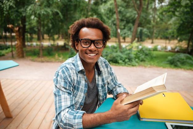 Vrolijke jonge man zitten en lezen van boek buitenshuis