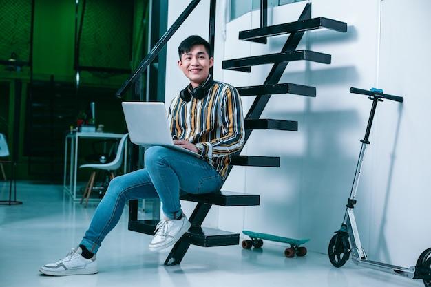 Vrolijke jonge man zittend op een trap met een laptop en wegkijkend met een glimlach. skateboard en een scooter achter zijn rug