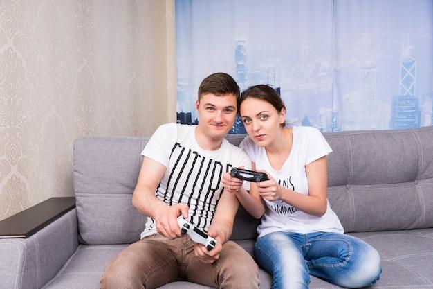 Vrolijke jonge mannelijke en vrouwelijke gamers die videogames spelen die samen thuis op een bank zitten in een ontspannen sfeer
