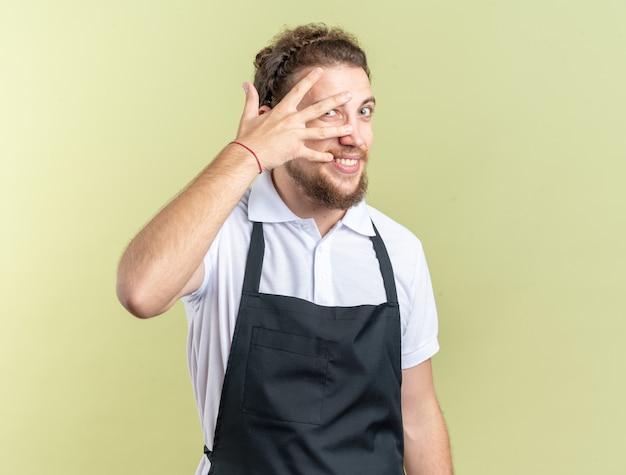 Vrolijke jonge mannelijke kapper met uniform bedekt gezicht met handen geïsoleerd op olijfgroene muur