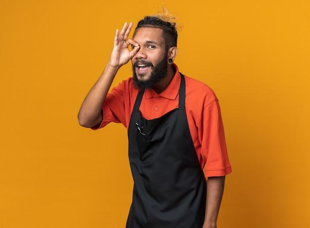 Vrolijke jonge mannelijke kapper met uniform staand in profielweergave kijkend naar de voorkant en doet een gebaar geïsoleerd op een oranje muur met kopieerruimte