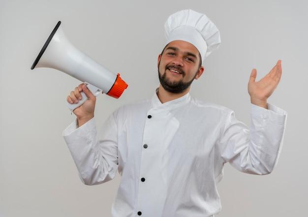 Vrolijke jonge mannelijke kok in uniform van de chef-kok die spreker houdt en hand opsteekt die op witte muur wordt geïsoleerd
