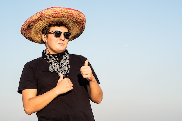 Vrolijke jonge mannelijke persoon in sombrero op heldere hemelachtergrond. mexico onafhankelijkheids feestelijk concept van feestende man met nationale mexicaanse hoed en westerse stijl bandana