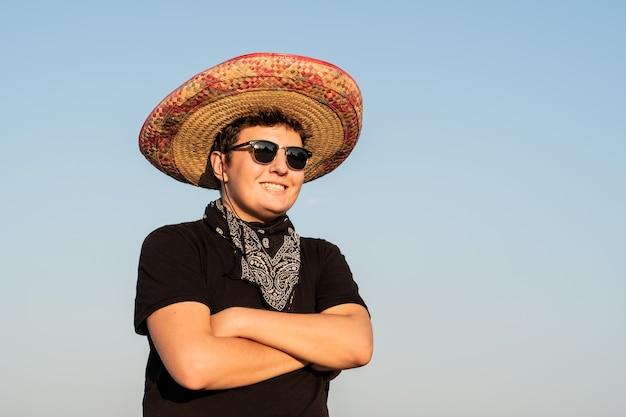 Vrolijke jonge mannelijke persoon in sombrero op heldere hemelachtergrond. mexico onafhankelijkheids feestelijk concept van man met nationale mexicaanse hoed en westerse stijl bandana