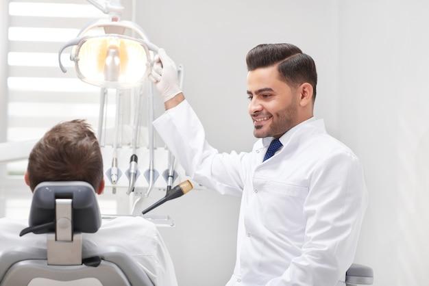 Vrolijke jonge mannelijke tandarts die bij zijn mannelijke patiënt glimlacht die voor tandonderzoek voorbereidingen treffen