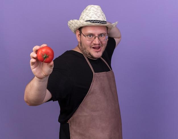 Vrolijke jonge mannelijke tuinman met een tuinhoed die tomaat uithoudt op camera geïsoleerd op een blauwe muur met kopieerruimte