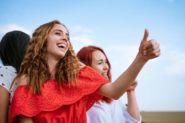 Vrolijke jonge meisjes dansen op de achtergrond van de lucht in de zomer