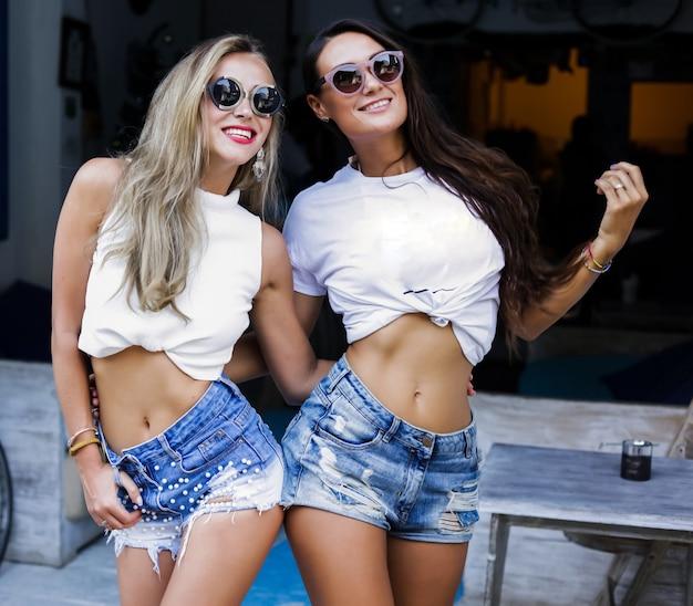 Vrolijke jonge meisjes die buiten witte t-shirts, moderne jeansborrels dragen. blonde en donkerbruine vrouwen. make-up en zonnebril op het gezicht. slanke lichamen, platte buiken. accessoires.