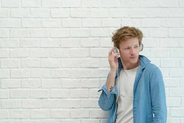 Vrolijke jonge mens die aan muziek met hoofdtelefoons met witte achtergrond luistert