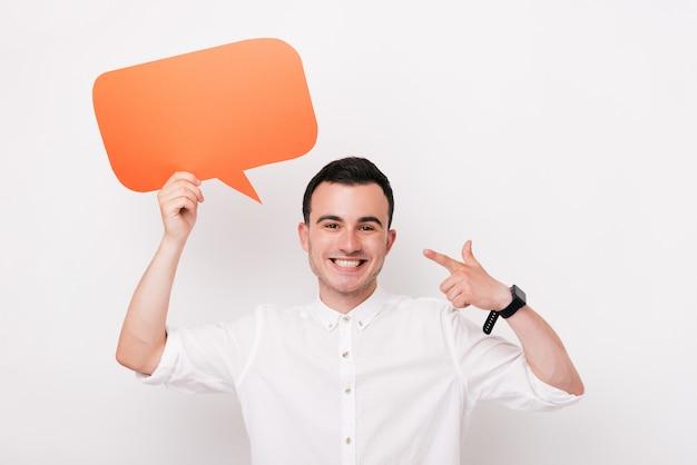 Vrolijke jonge mens die een dialoogwolk of een rechthoekige oranje bellentoespraak op witte achtergrond houden.