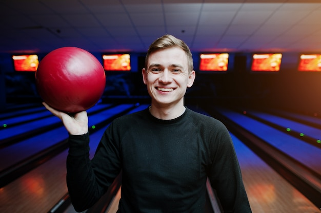 Vrolijke jonge mens die een kegelenbal houdt en bij camera glimlacht terwijl status tegen kegelbanen met ultraviolet licht.