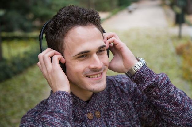 Vrolijke jonge mens die en zich aan muziek met hoofdtelefoons in de herfstpark bevinden luisteren.