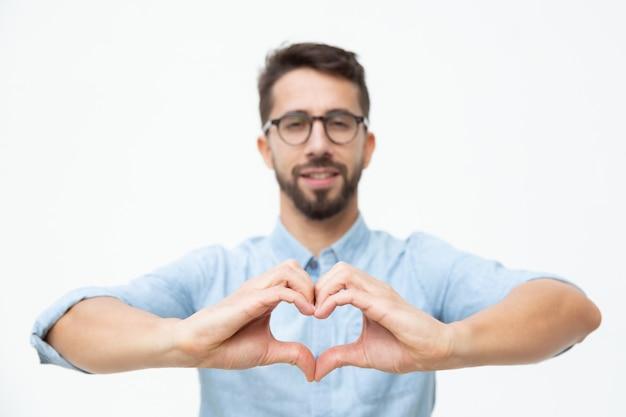Vrolijke jonge mens die het gebaar van het handhart tonen