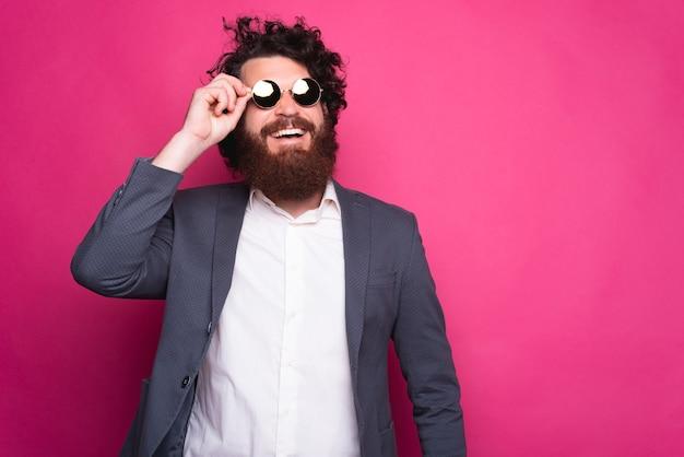 Vrolijke jonge mens die met zonnebril glimlacht