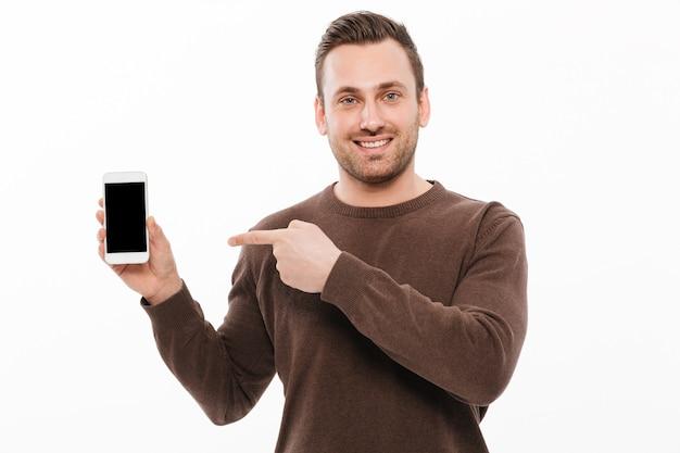 Vrolijke jonge mens die vertoning van mobiele telefoon toont