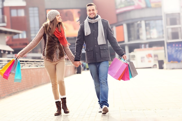 Vrolijke jonge mensen lopen met boodschappentassen in de stad