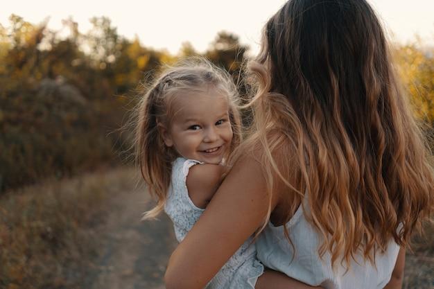 Vrolijke jonge moeder brengt heerlijke vakantietijd door in het bos met haar kind. twee blondies, moeder en dochter