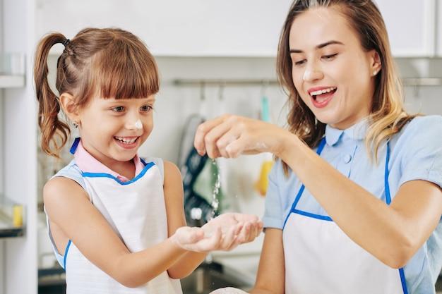 Vrolijke jonge moeder en haar preteen dochter die met bloem in keuken spelen bij het samen koken van diner